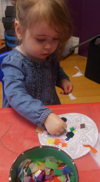 Sticking different coloured pieces of paper on the Rangoli patterns