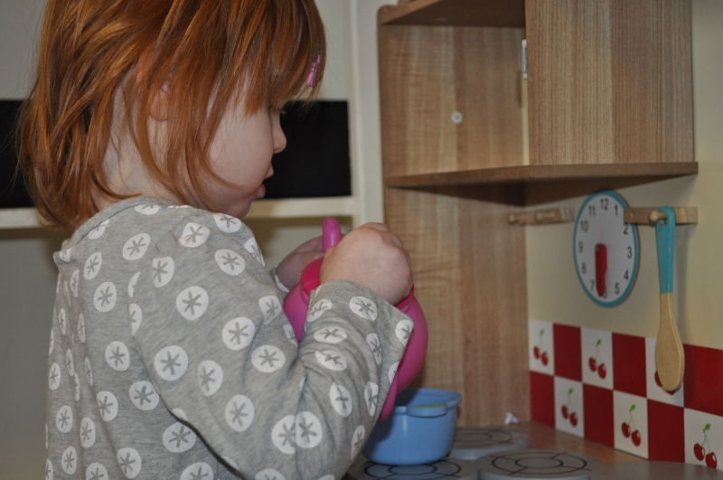 Pretending to make dolly a cup of tea
