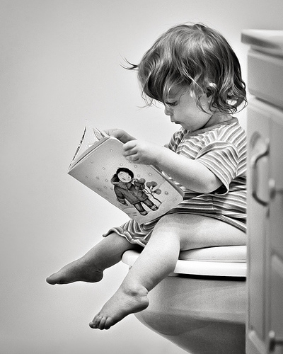 child sitting on toilet