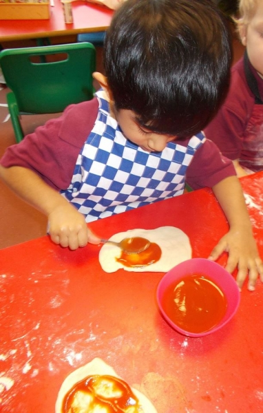 Using the spoon to spread on the tomato puree