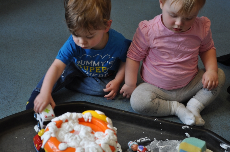 Playing with the cars in the shaving foam