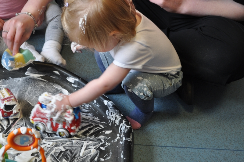 Pushing the toy cars in the shaving foam