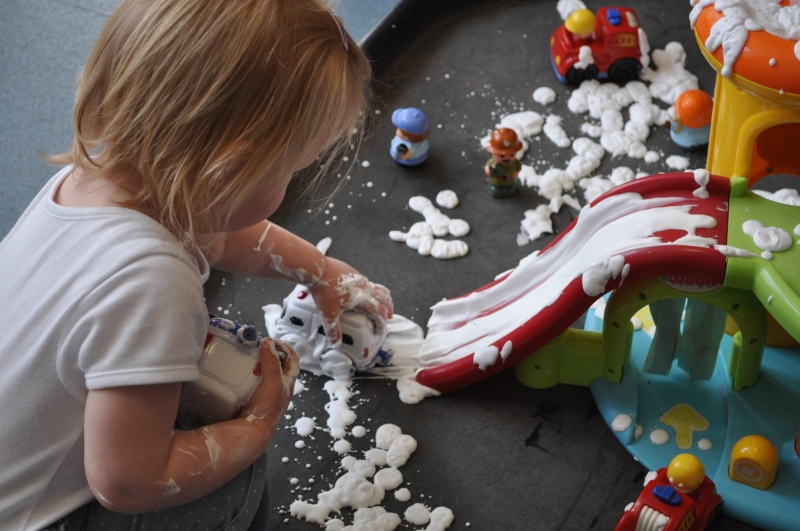 Pushing the toys cars along in the shaving foam
